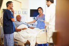 Medical team meeting with senior man in hospital room Stock Photos