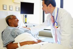 Doctor talking to senior woman in hospital room Stock Photos