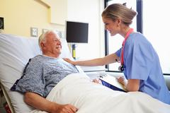 Nurse talking to senior male patient in hospital room Stock Photos