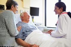 Female doctor talking to senior couple in hospital room Stock Photos