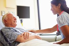 Female doctor talking to senior man in hospital room Stock Photos