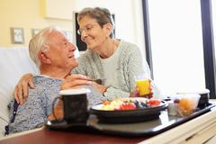 Senior couple in hospital room as male patient has lunch Stock Photos