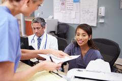 medical staff meeting at nurses station - stock photo