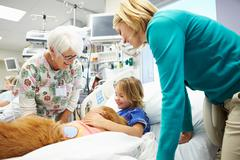 Young girl being visited in hospital by therapy dog Stock Photos