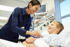 boy being examined by female consultant in emergency room - stock photo