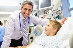 boy talking to male consultant in emergency room - stock photo