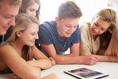 Group of teenagers gathered around digital tablet together Stock Photos