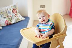 baby boy sitting in high chair - stock photo