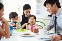 Asian family having breakfast before husband goes to work Kuvituskuvat