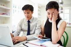 Worried asian couple looking at personal finances Stock Photos