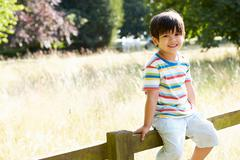 Portrait of asian boy sitting on fence in countryside Stock Photos