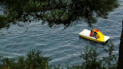 Tourists driving a pedal boat at sea Stock Footage