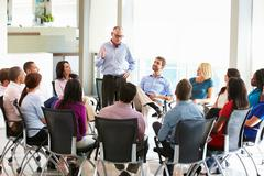 businessman addressing multi-cultural office staff meeting - stock photo