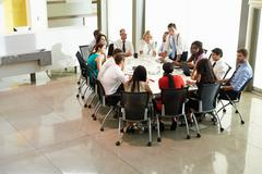 Businessman addressing meeting around boardroom table Stock Photos