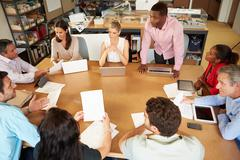 Architects sitting at table meeting with laptops and tablets Stock Photos