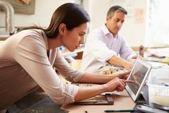 Two architects making models in office using digital tablet Stock Photos