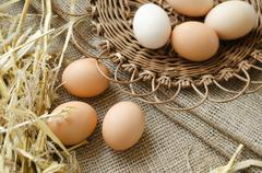 Brown eggs in a wicker plate and sackcloth - stock photo