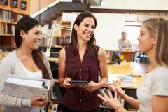 Three female architects chatting in modern office together Stock Photos
