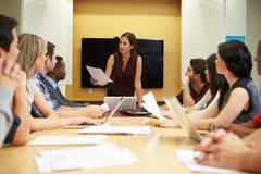 Female boss addressing meeting around boardroom table Stock Photos