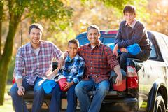 Fathers with sons sitting in truck on camping holiday Stock Photos
