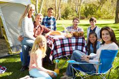Two families enjoying camping holiday in countryside Stock Photos