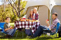 Family enjoying camping holiday in countryside Stock Photos