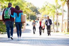 Student couple walking outdoors on university campus Kuvituskuvat