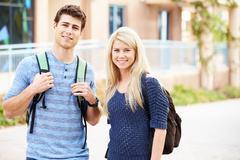 Male and female university students outdoors on campus Kuvituskuvat