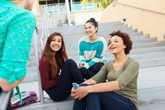 Female high school students sitting outside building Kuvituskuvat