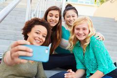 Female high school students taking selfie photograph Kuvituskuvat