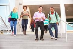 high school pupils and teacher on steps outside building - stock photo