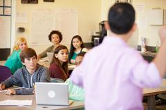 High school students with teacher in class using laptops Kuvituskuvat