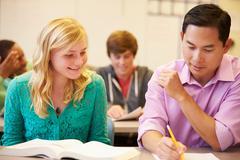 High school teacher helping student with written work Stock Photos