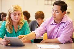 High school student with teacher using digital tablet Stock Photos
