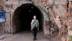 Tourists walking along the coast and through the tunnel Stock Footage