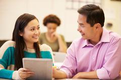 High school student and teacher using digital tablet Stock Photos