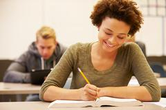 Female high school student studying at desk in classroom Stock Photos