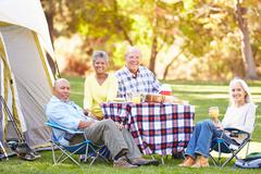 Two senior couples enjoying camping holiday in countryside Stock Photos