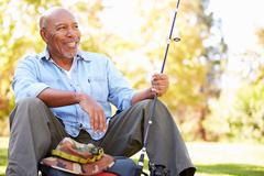 Senior man on camping holiday with fishing rod Stock Photos