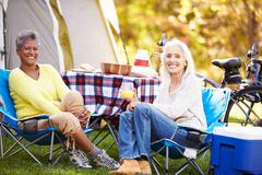 Two mature women relaxing on camping holiday Stock Photos