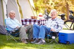 Two senior men relaxing on camping holiday Stock Photos