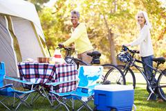 Two mature women riding bikes on camping holiday Stock Photos