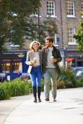 Couple walking through park with takeaway coffee Stock Photos