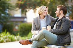 Couple relaxing on park bench with takeaway coffee Stock Photos