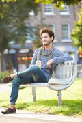 Man relaxing on park bench with takeaway coffee Stock Photos