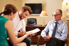 Young couple talking to financial advisor in office Stock Photos