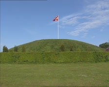 Danish flag flying on top of Jelling North Mound + pan Church and South Mound Stock Footage
