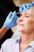Woman having botox treatment at beauty clinic Stock Photos