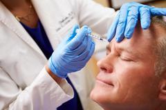 Man having botox treatment at beauty clinic Stock Photos