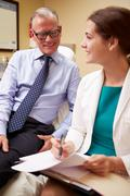 Female doctor in consultation with male patient Stock Photos